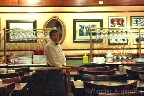 a waiter standing behind the bar of a cafe in buenos aires