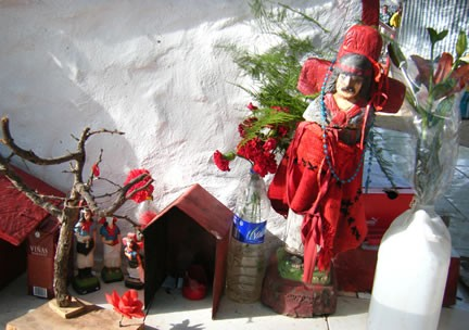 A simple shrine to Guachito Gil, Argentina's cowboy saint, with a figurine, rosary and flowers in Buenos Aires, Argnetina