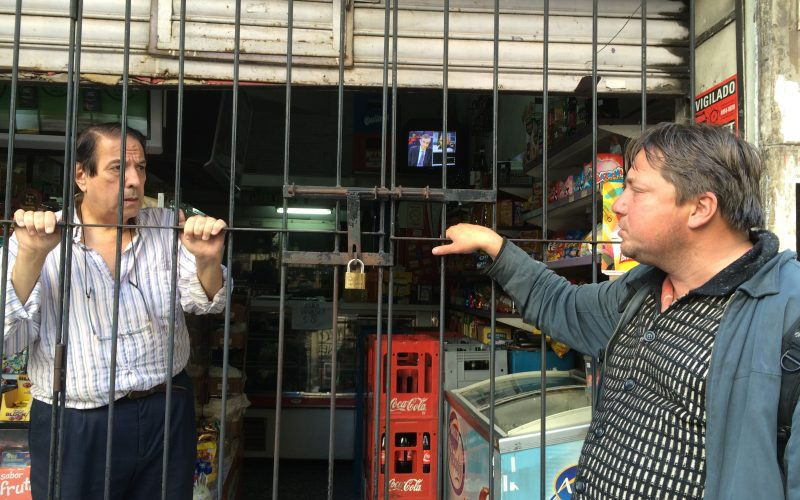 A kiosk owner behind the bars of his store, and Fabian, a Dutch scammer who lives on the street in Buenos Aires and poses as a distressed traveler to scam tourists out of money so that he can buy beer.