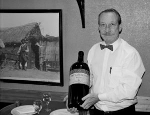 Long time Broccolino waiter Nicolas displays a giant bottle of wine
