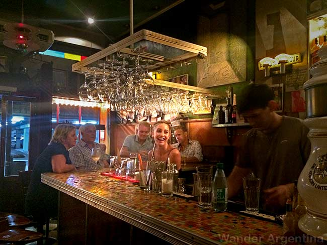 The bartender smiles at colorful tiled bar at Dadá bar and restaurant in Buenos Aires.
