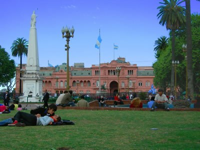 A couple lounges in front of Buenos Aires' Casa Rosada, or government house