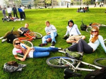 A smiling group on a bike tour in Buenos Aires take a break to relax on the grass in a park