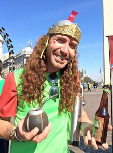 A red-headed man in Buenos Aires holds a gourd for mate tea and a beer