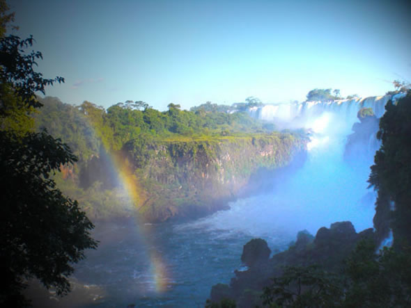 Iguazu Falls on the Argentina side, with a rainbow in the foreground.