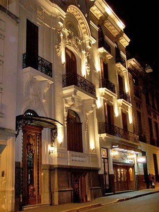 The lit up exterior of the turn of the 19th century Mansion Royal Dandi hotel in Buenos Aires