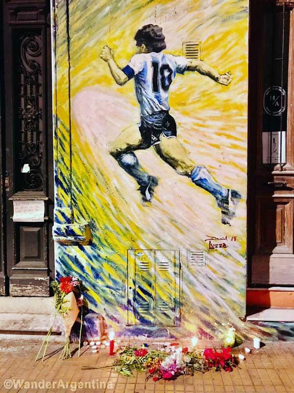 Graffiti of Diego Maradona with flowers underneath