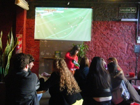 A group huddles around the bar to watch a game at Sugar bar in Palermo