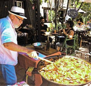 A man cooking a big pan of paella outdoors at a restaurant in Colonia del Sacramento, Uruguay,as customers look on from nearby tables.