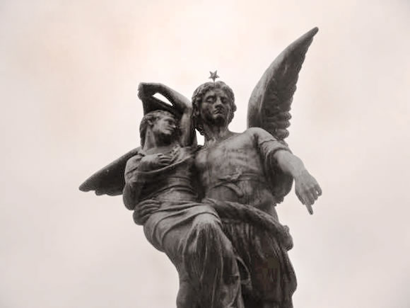 A beautiful statue of an angel atop a tomb in the famous Recoleta Cemetery of Buenos Aires