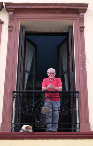 A resident and senior citizen in San Telmo, Buenos Aires admiring the view from his French balcony.