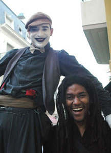 A mime on stilts poses with an American tourist at the San Telmo fair