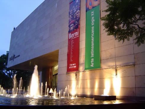 The outside of Buenos Aires' MALBA museum at night, with water fountain in front