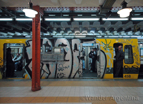 The outside of a Buenos Aires Subway car in the station with graffiti