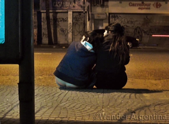 Two girls waiting for the bus on Corrientes ave. in Buenos Aires