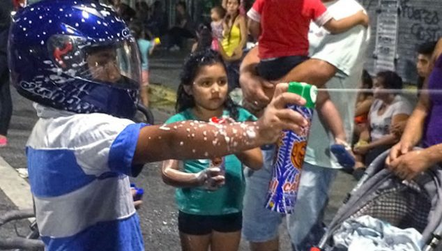 A child with a motorcycle helmet sprays foam from a can on the streets of Buenos Aires during Carnival celebrations
