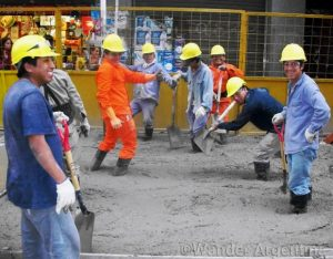 contruction workers in buenos aires knee deep in cement