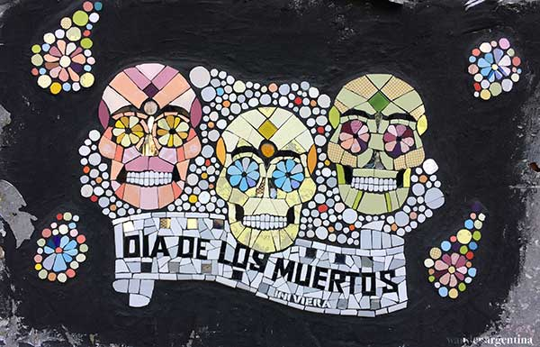 A mosaic with skulls that says 'Day of the Dead'
