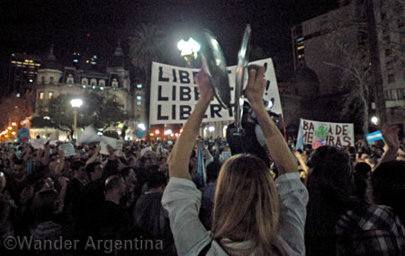 A woman bangs pot lids in a cacerolazo protest in the Plaza de Mayo