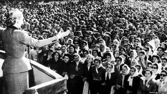 Black & white photo of Evita addressing the crowd from the balcony of the Casa Rosada