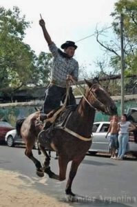 An Argentine cowboy on a horse holds up the ring he won in the corrida de sortijas