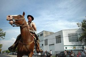 A smiling Argentine cowboy on a horse