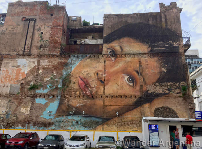 Large mural of realist graffiti of a boy's face in Buenos Aires