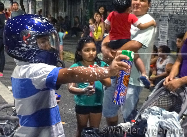 A boy at Buenos Aires' carnival wears a helmet while spraying chemical 'snow' at other kids