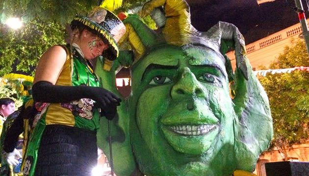 Carnival dancer in Buenos Aires checks her cellphone next to a large Carnival mask
