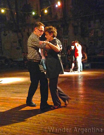 A couple dances tango on the dance floor at La Catedral de Tango in Buenos Aires