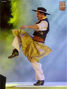 A man in a traditional Argentine folk dance costume preforms fancy footwork on stage at the Cosquin Folklore Festival in Argentina