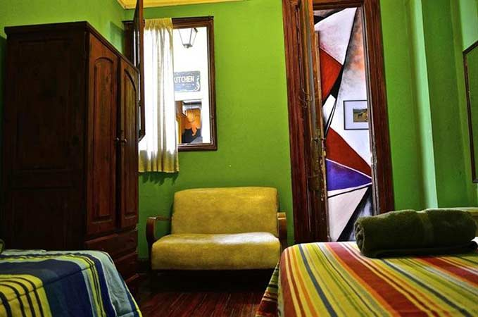 A room with two beds and a chair at Art Factory Hostel in Buenos Aires