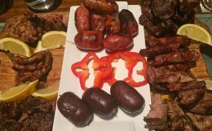 An asado (Argentine barbecue) appetizer of sausages and organ meatss