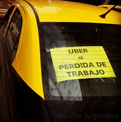 A sign in the window of a Buenos Aires taxi says (in Spanish) Uber= Loss of Work