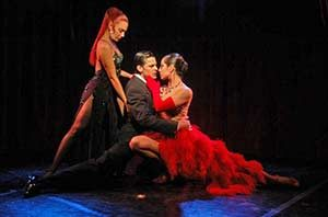 Two women and a male dancer perform a tango move at the Rojo Tango Show.