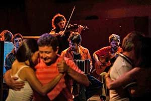 Couples dance tango with an orchestra in the background in a Buenos Aires milonga