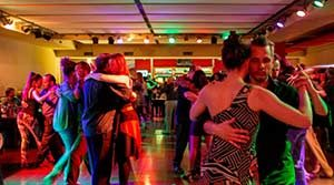 Couples embraced, dancing tango in a Buenos Aires milonga