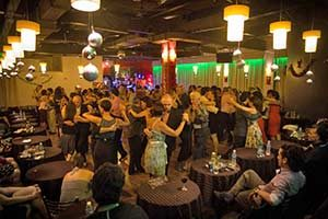 As people sit at tables in the foreground, a roomful of couples dance tango in the background at a Buenos Aires milonga, or tango dancehall