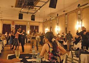 A woman looks on as couples embraced on the dance floor dance tango in a milonga, or tango dancehall of Buenos Aires