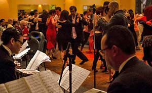 a picture of a milonga (tango dancehall) with musicians in the foreground and couples dancing tango in the background.